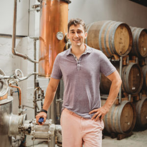 Ben Bonoma Staff Photo In Front Of The Still And Wooden Barrels